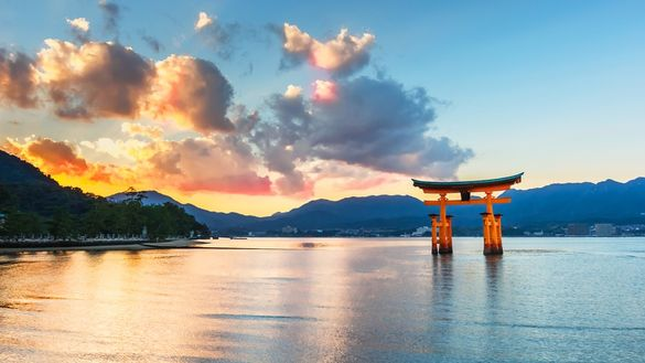 Photograph the iconic scarlet torii, a giant camphor-wood gate at the entrance to the Itsukushima Shrine, a World Heritage Site and a sacred site of pilgrimage. At high tide it appears to float in the surrounding waters.