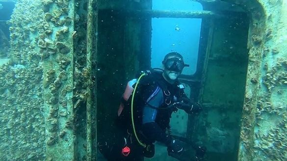 A Hervey Bay Dive Centre staff member has an early look at the ex-HMAS Tobruk wreck.